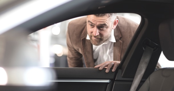 Image of man looking into car
